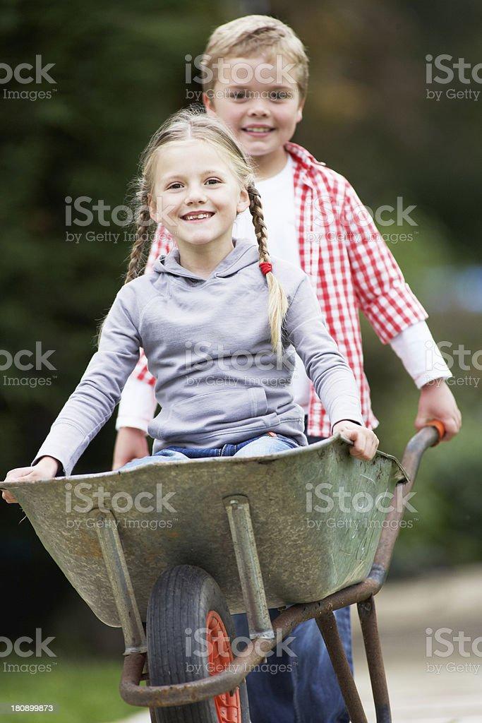 Boy Giving Girl Ride In Wheelbarrow stock photo