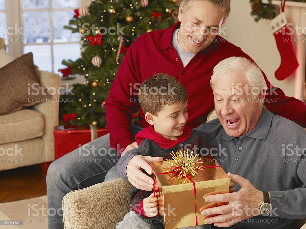Boy giving grandfather Christmas gift royalty-free stock photo
