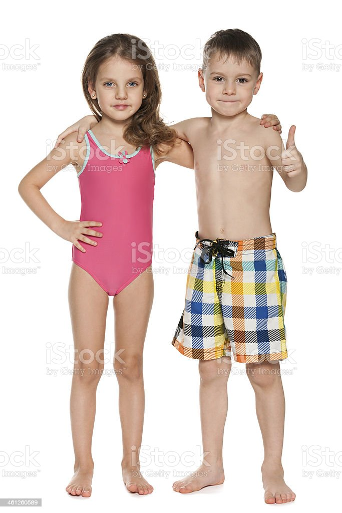 Boy giving thumbs up next to girl who are both in swimsuits stock photo