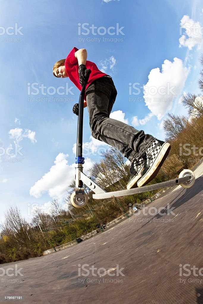 Boy going airborne with a scooter stock photo
