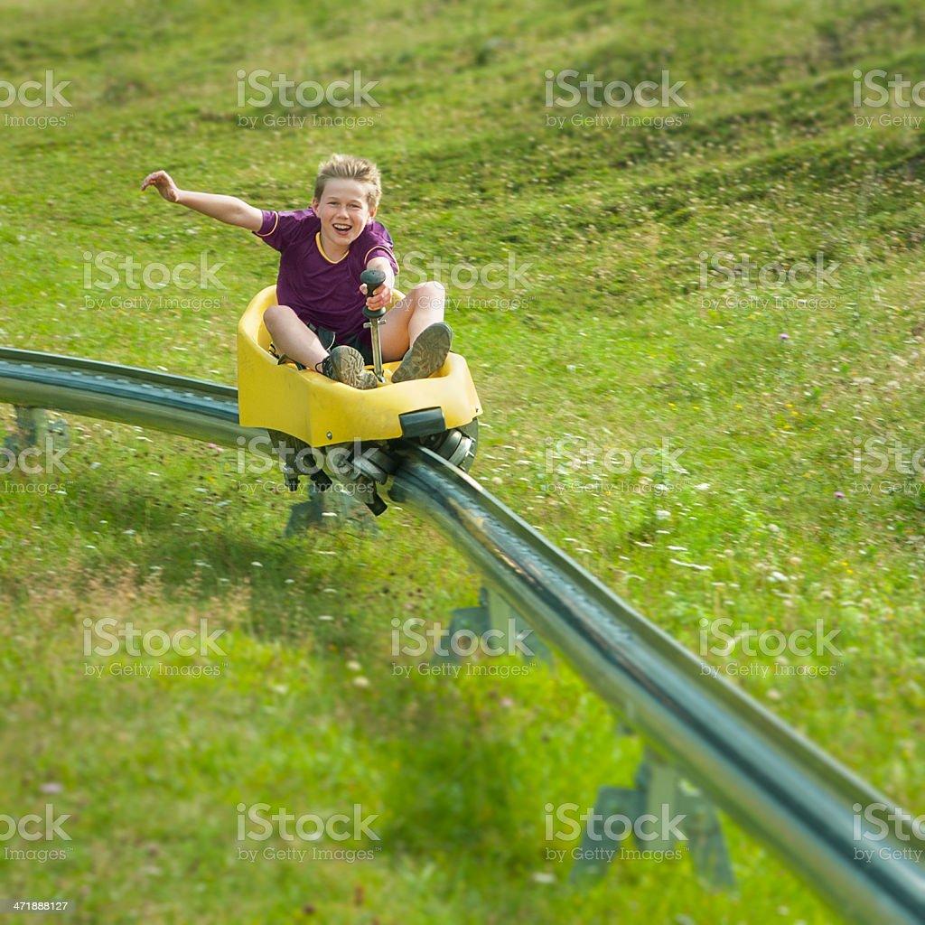 Boy going downhill at summer toboggan run stock photo