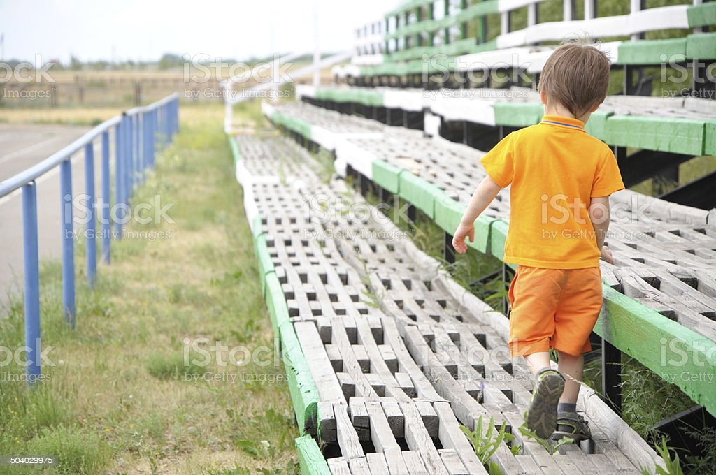 boy going through the empty benches in the stadium royalty-free stock photo