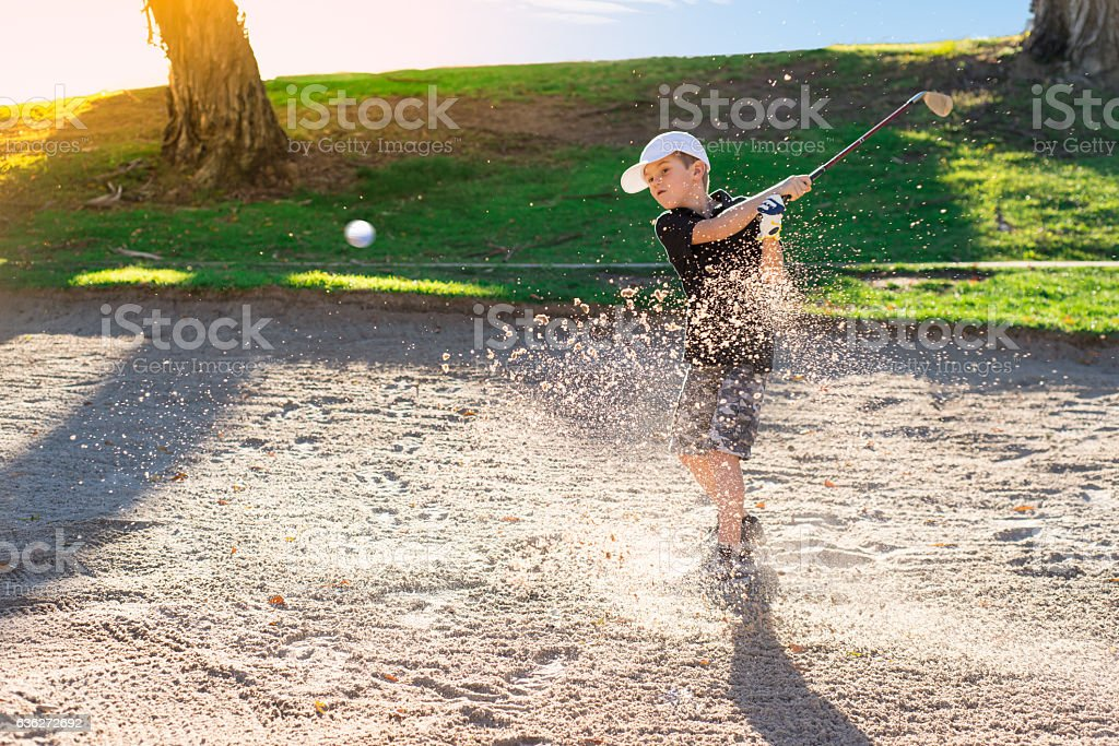 Boy Golfer Hitting Out A Sand Bunker stock photo