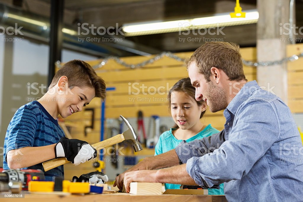 Boy hammers nail into board in woodworking shop stock photo