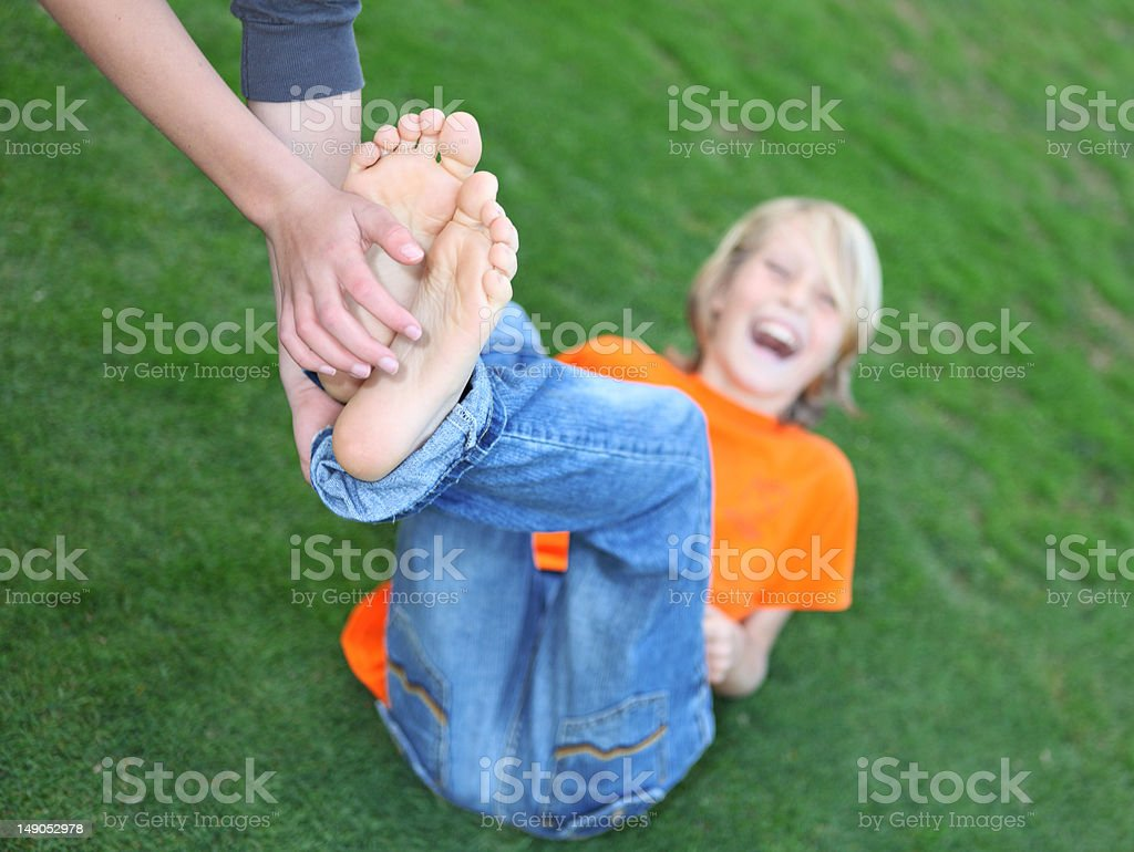 boy having feet tickled (PERSONAL REQUEST) selective focus on foot stock photo