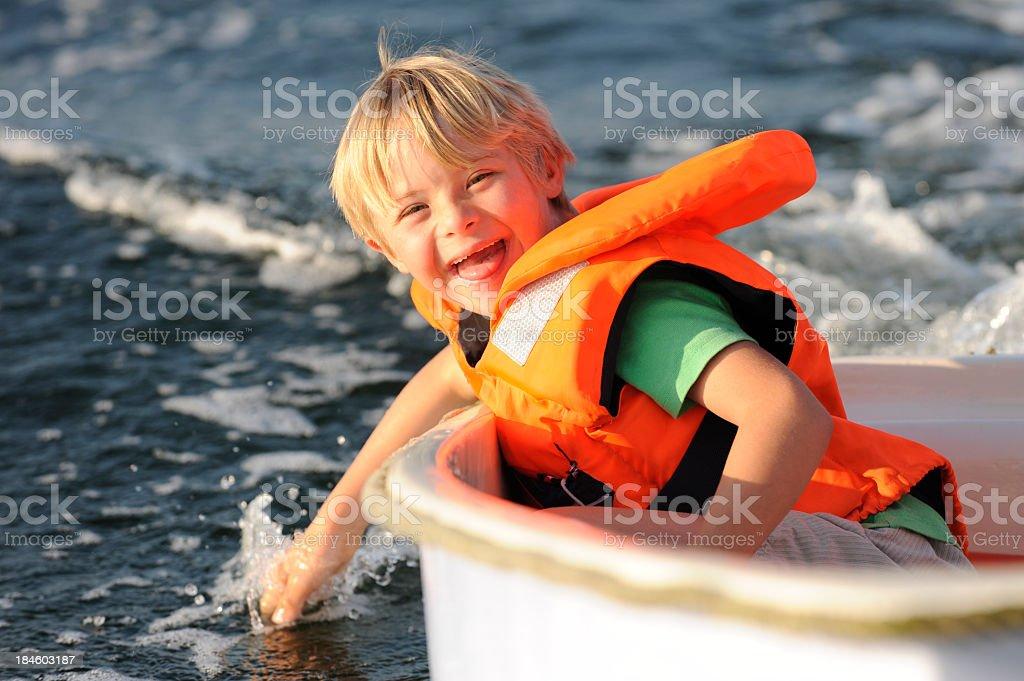 Boy having fun in a small boat stock photo