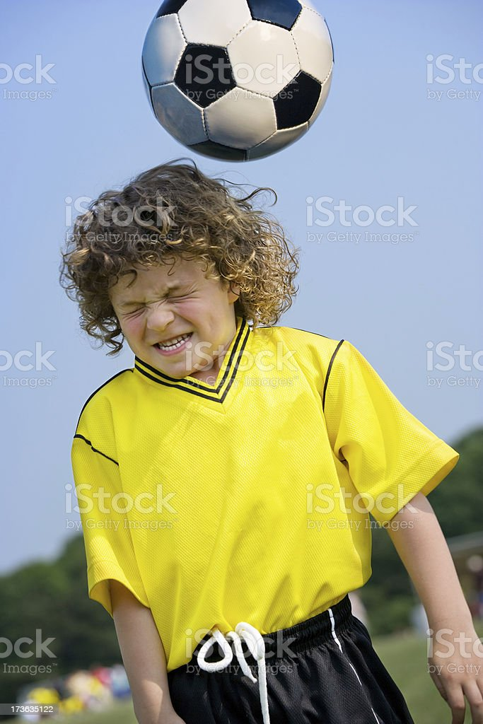 Boy heading soccer ball stock photo