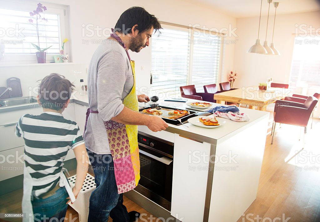 Boy helping father with serving food stock photo
