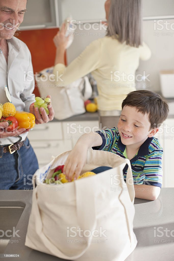 Boy helping to unload groceries from reusable bag stock photo