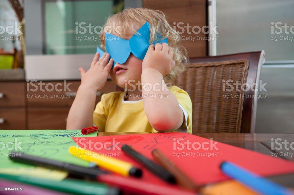 Boy hiding behind paper stock photo