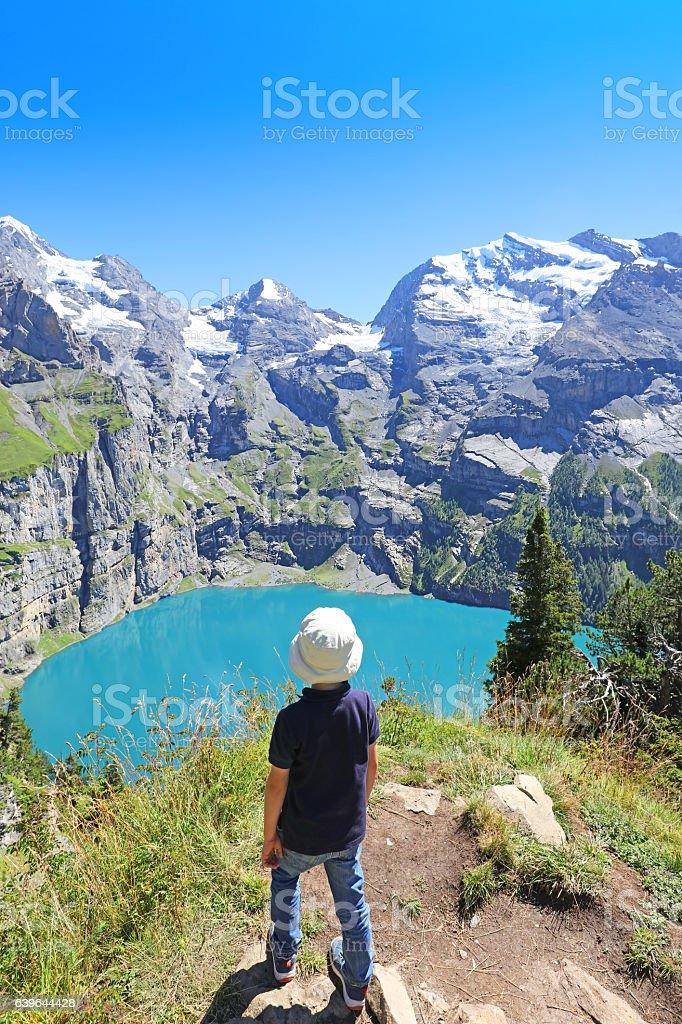Boy Hiker at Oeschinensee Lake Hiking Trail in Switzerland stock photo