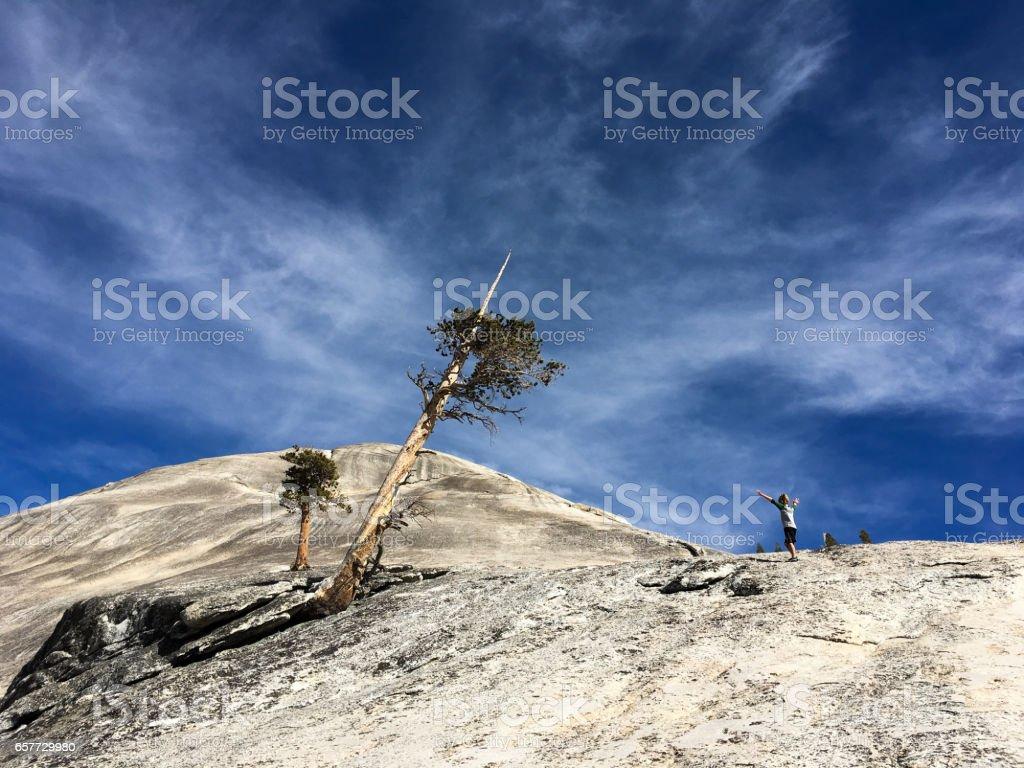 Boy hiking alone on large dome in Yosemite stock photo