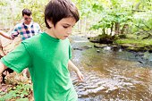Boy Hiking in Forest with Father Walking Behind Along Stream