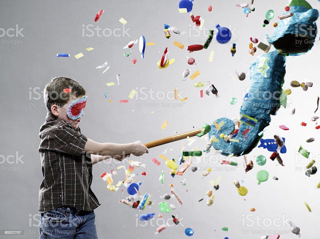 Boy hitting pinata, explosion of candy stock photo