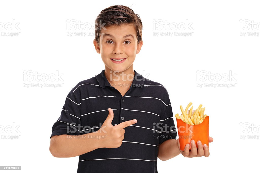 Boy holding a bag of fries and pointing stock photo