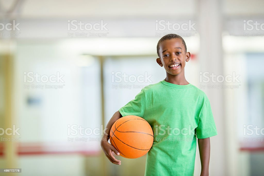 Boy Holding a Basketball After a Game stock photo