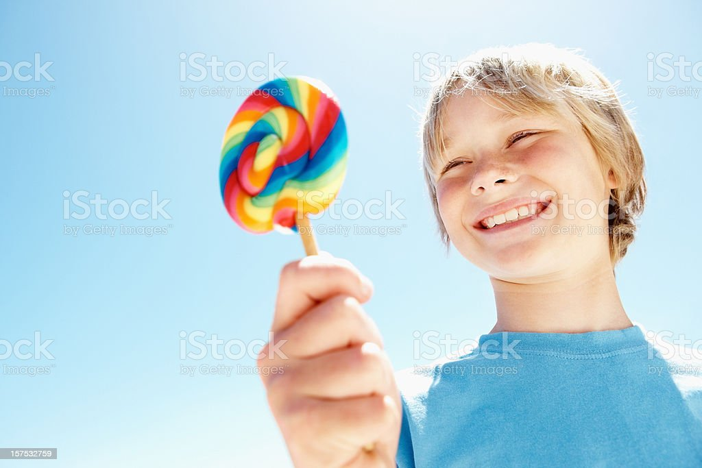 Boy holding a candy royalty-free stock photo