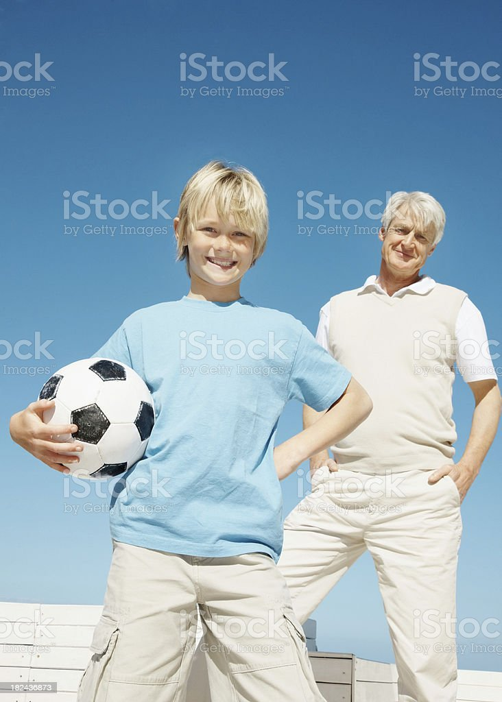 Boy holding a football with grandfather in the background royalty-free stock photo