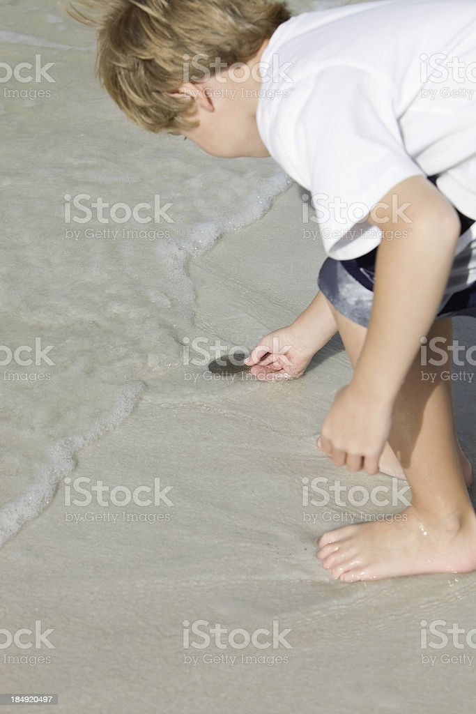 Boy Holding a Sand Dollar in Ocean Surf royalty-free stock photo