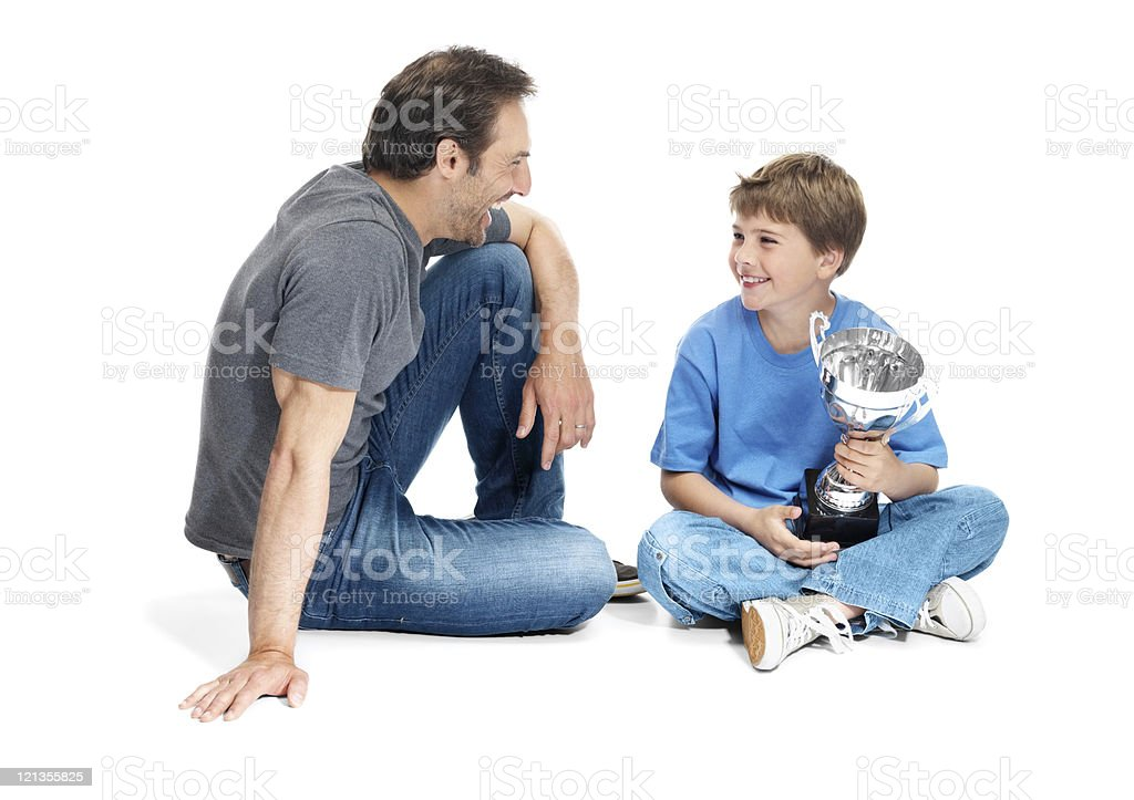 Boy holding a winning trophy and sitting beside his father royalty-free stock photo