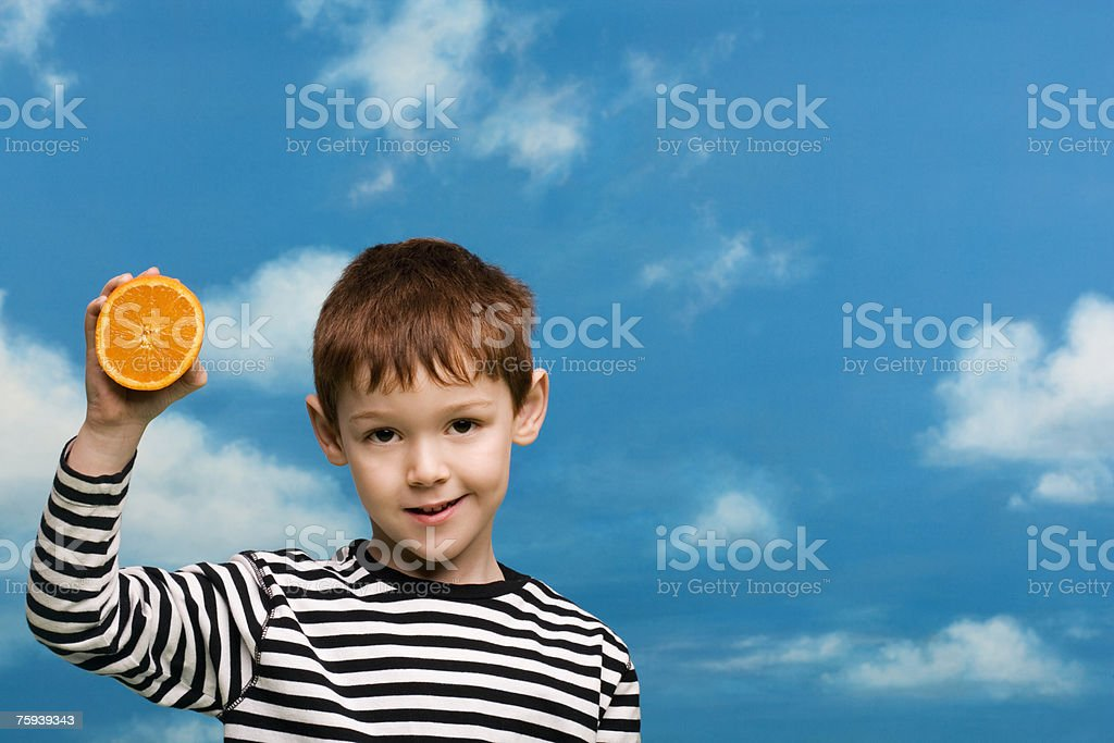 Boy holding an orange royalty-free stock photo