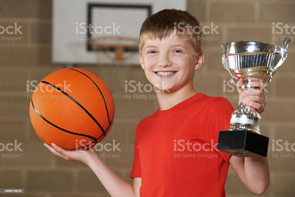 Boy Holding Basketball And Trophy In School Gymnasium stock photo