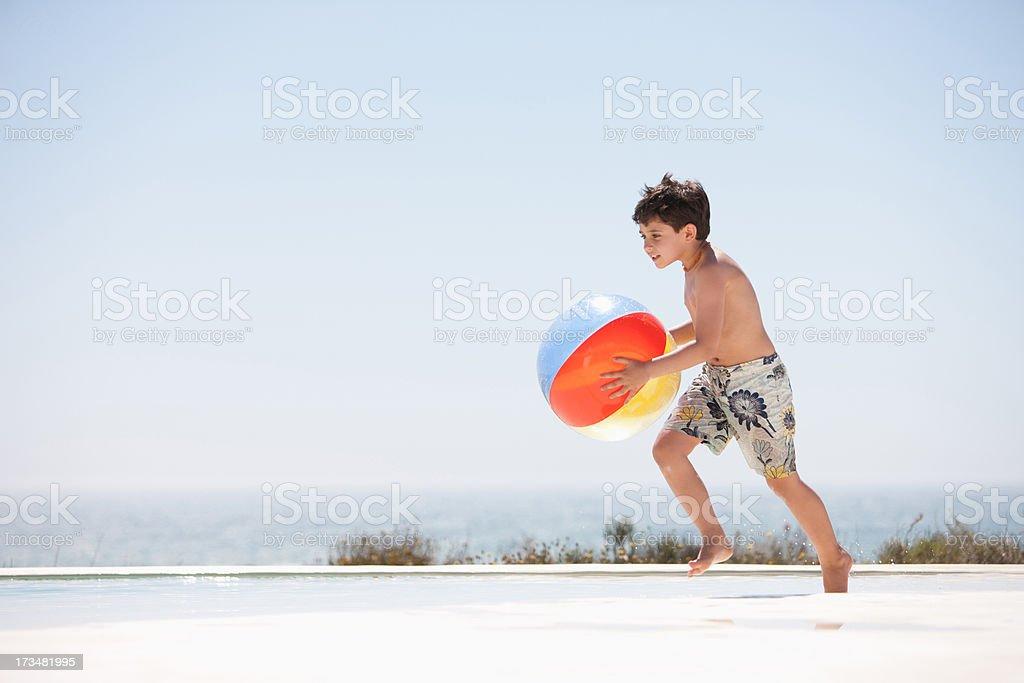 Boy holding beach ball beside pool royalty-free stock photo