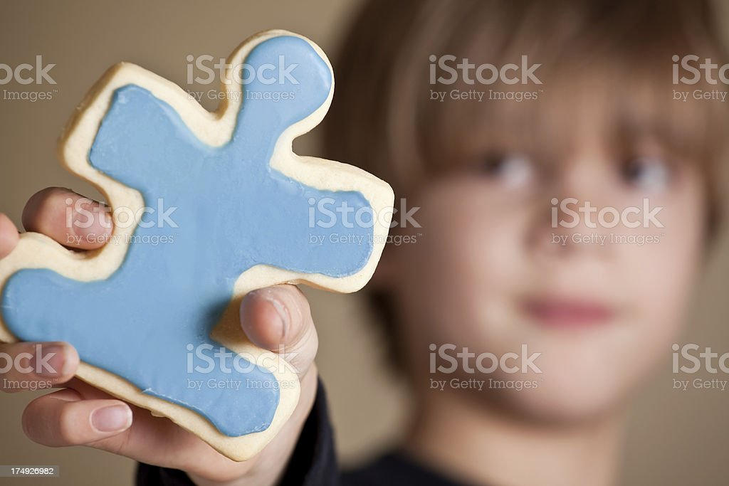Boy Holding Blue Iced Puzzle Piece Cookie stock photo