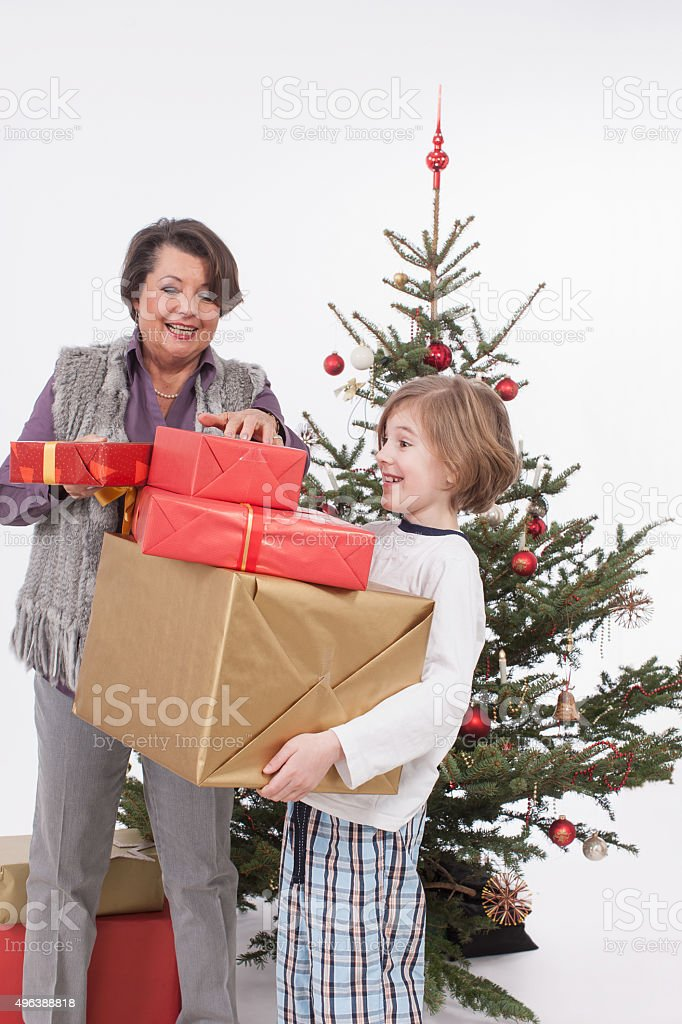 Boy holding Christmas gifts while senior woman adjusting, smilin stock photo