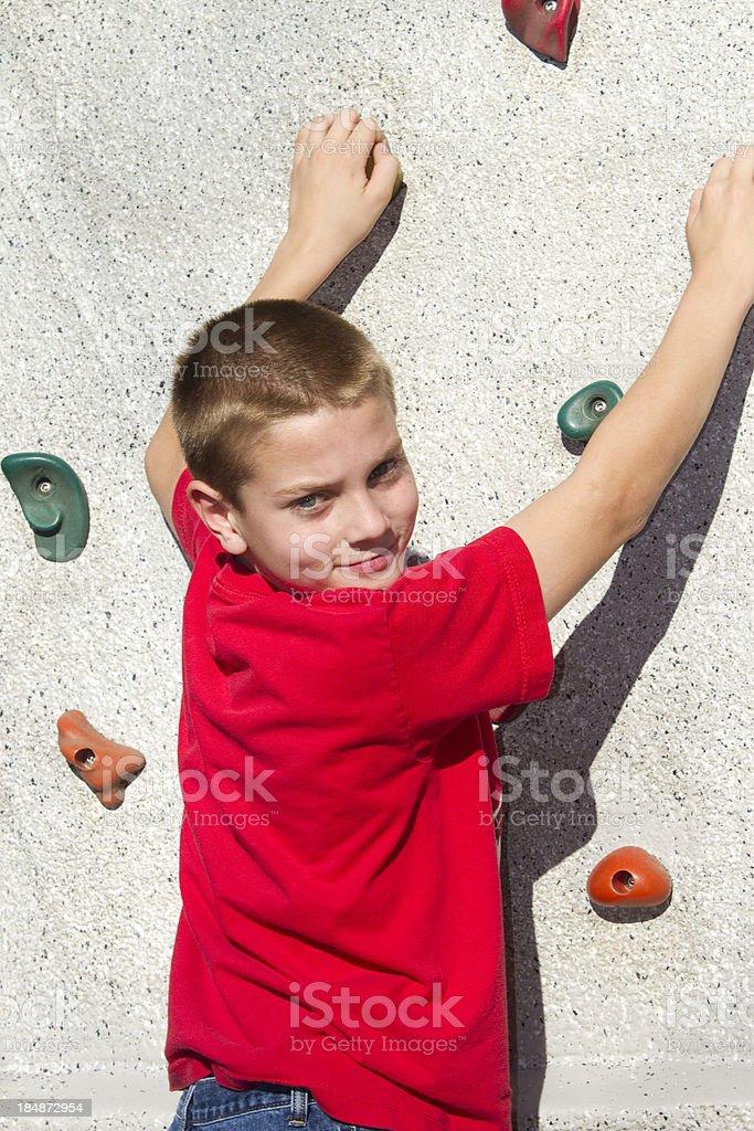 Boy Holding Climbing Rock Wall, Looking Back royalty-free stock photo