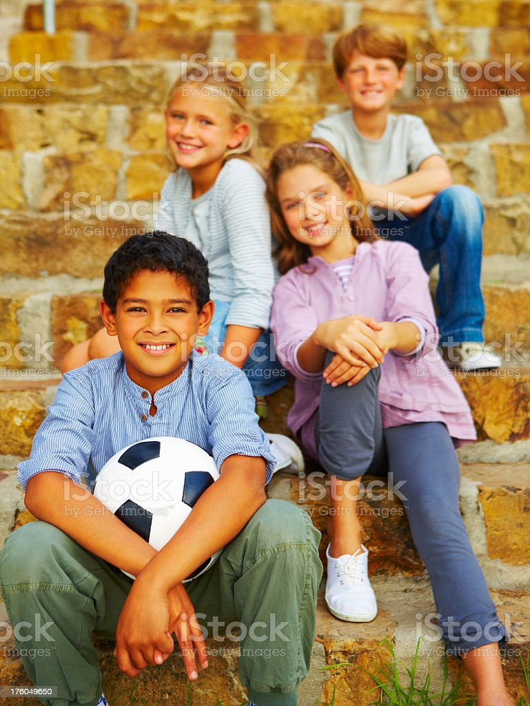 Boy holding football and sitting with his friends royalty-free stock photo