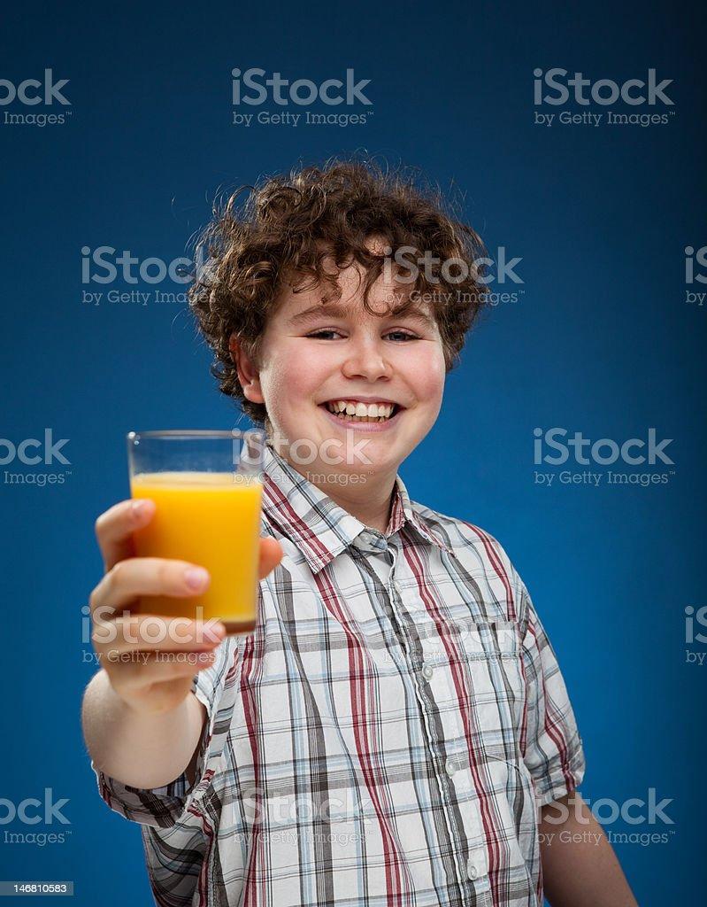 Boy holding glass of orange juice stock photo