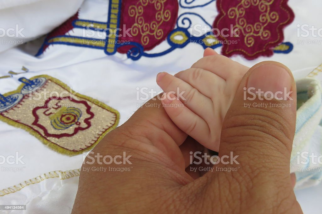 boy holding his father's hand during circumcision stock photo