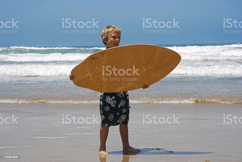 Boy holding his skimboard stock photo