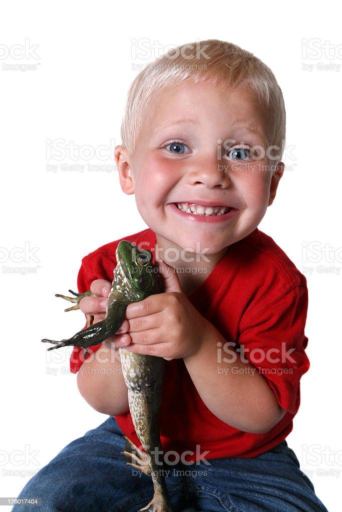Boy holding large bullfrog while sitting and smiling royalty-free stock photo