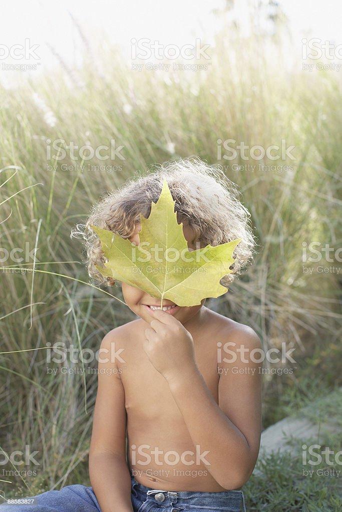 Boy holding leaf outdoors royalty-free stock photo