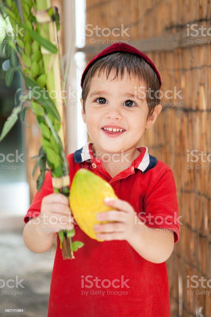 Boy holding lulav and etrog for Sukkot stock photo