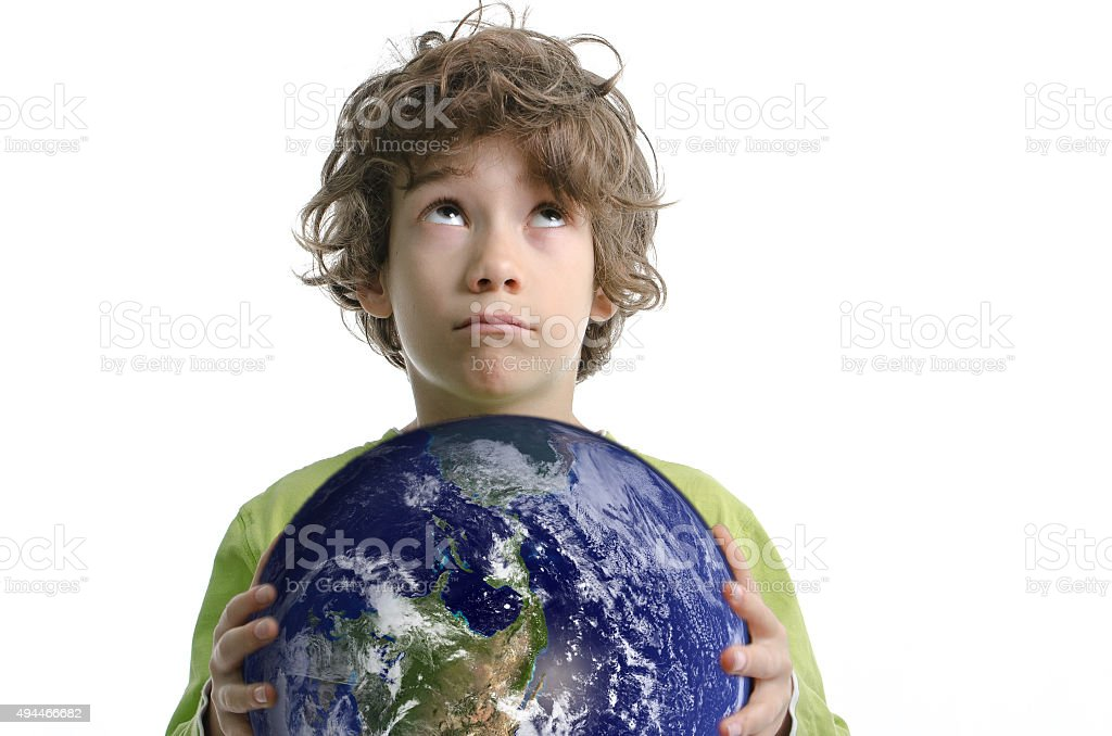 Boy holding planet Earth in his hand with eyes up stock photo