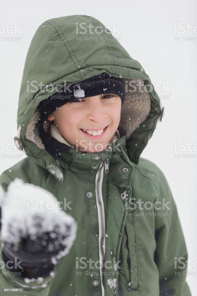 Boy holding snowball stock photo