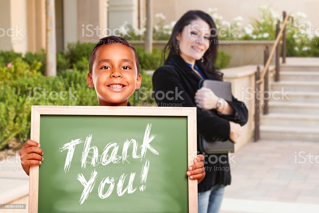 Boy Holding Thank You Chalk Board with Teacher Behind stock photo
