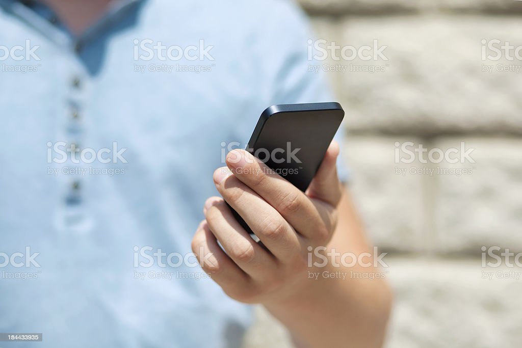 boy holding touch phone against a wall royalty-free stock photo