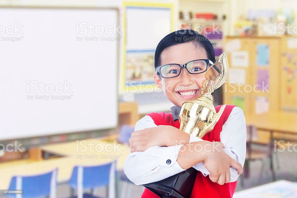 Boy holding trophy in classroom stock photo