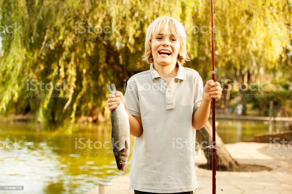 Boy holding up fish royalty-free stock photo