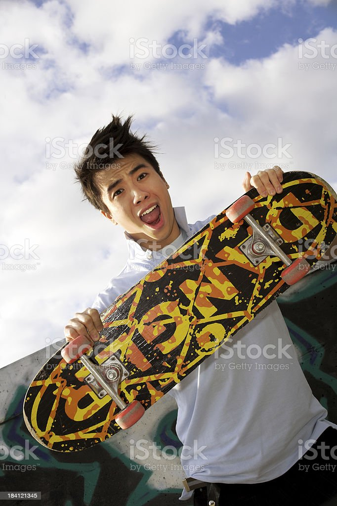 A boy holding up his skateboard against the white clouds royalty-free stock photo