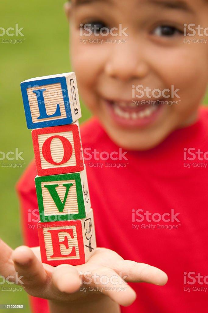Boy holding word 'LOVE' royalty-free stock photo