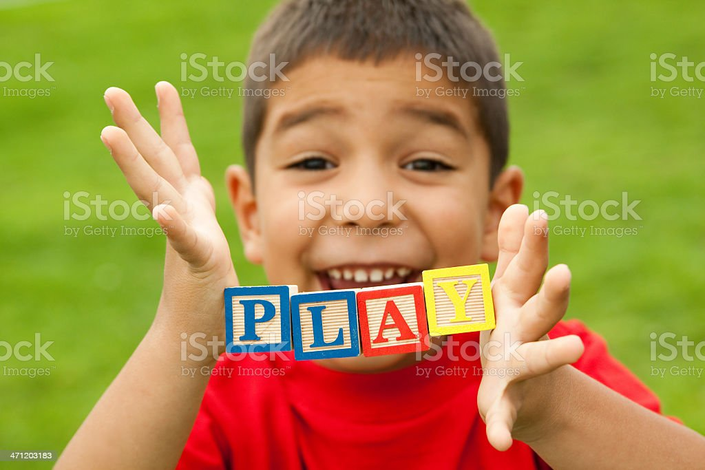 Boy holding word 'play' royalty-free stock photo