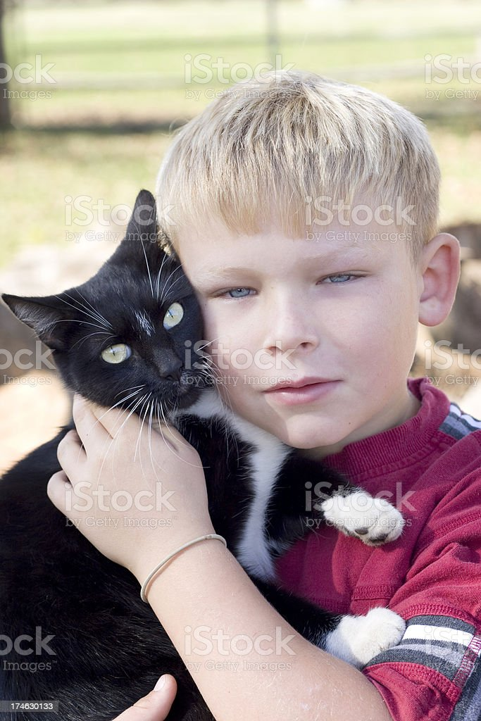 Boy holds Black and White Cat stock photo