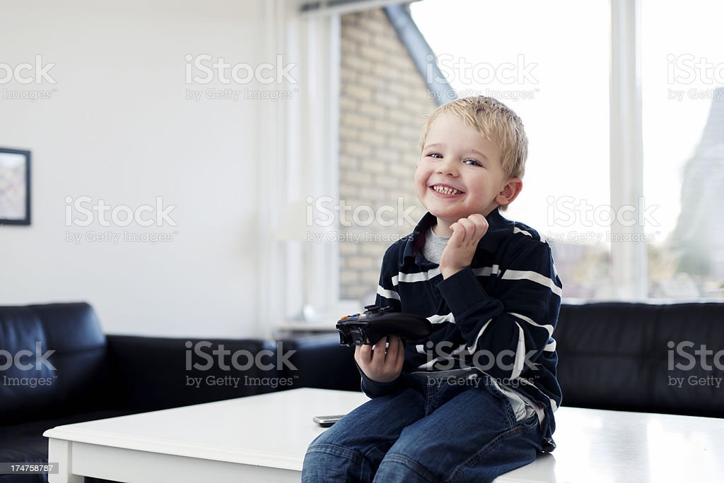 Boy holds joystick and plays video game royalty-free stock photo