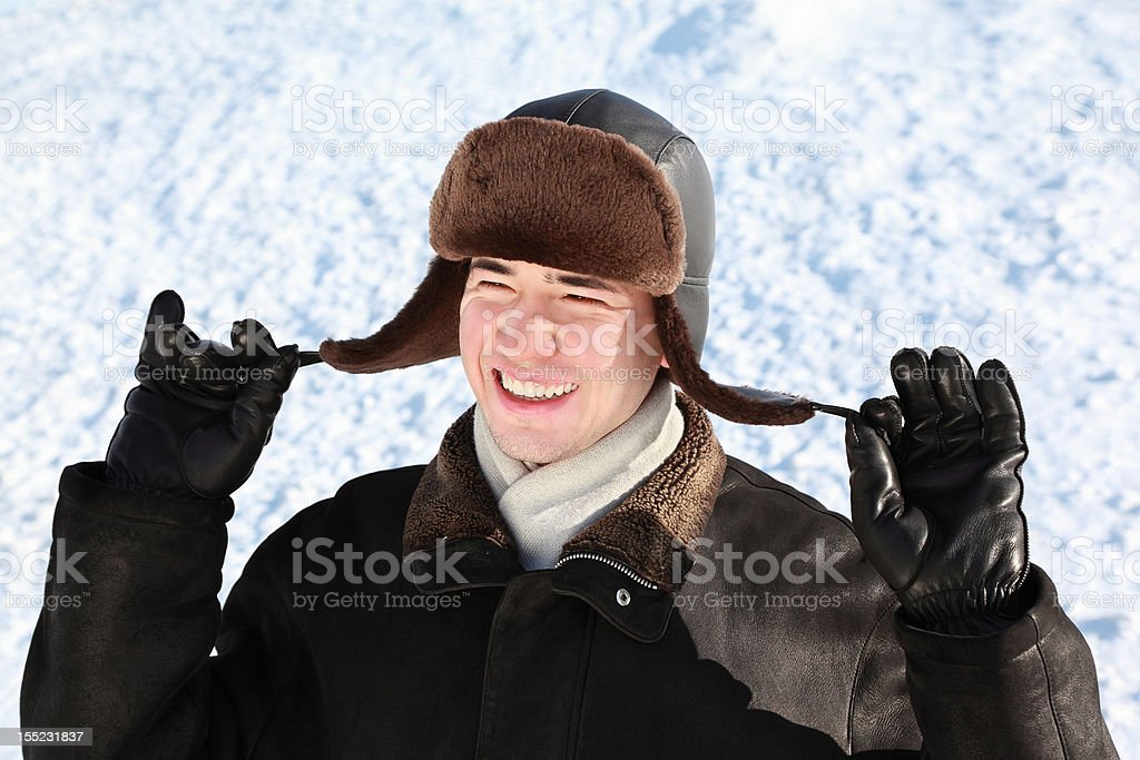 Boy holds on cordages ear-flaps hat stock photo