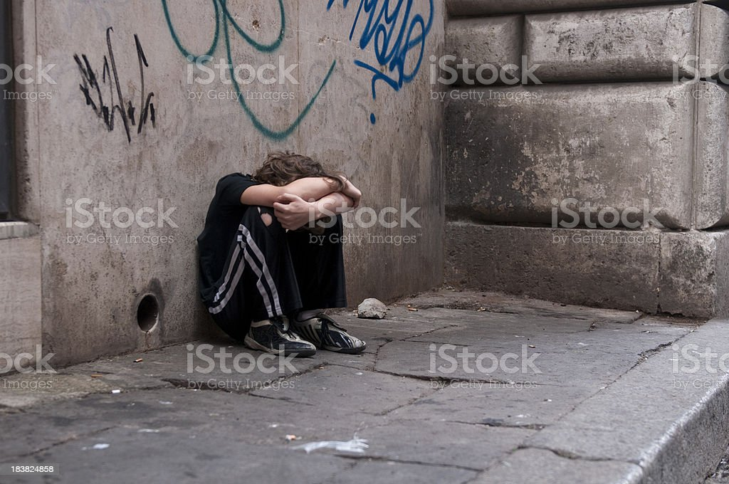 Boy huddled and alone on city street royalty-free stock photo
